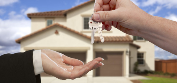 Handing Over the House Keys in Front of a Beautiful New Home.